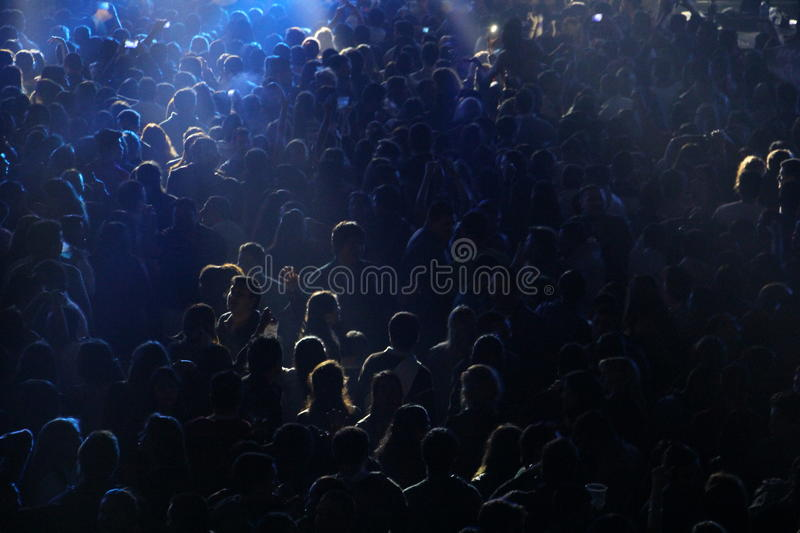Crowd at concert or party. People at concert or show, all together, party having fun, happy, night, drinking with friends. Blue lights, dark environment, against stock photo