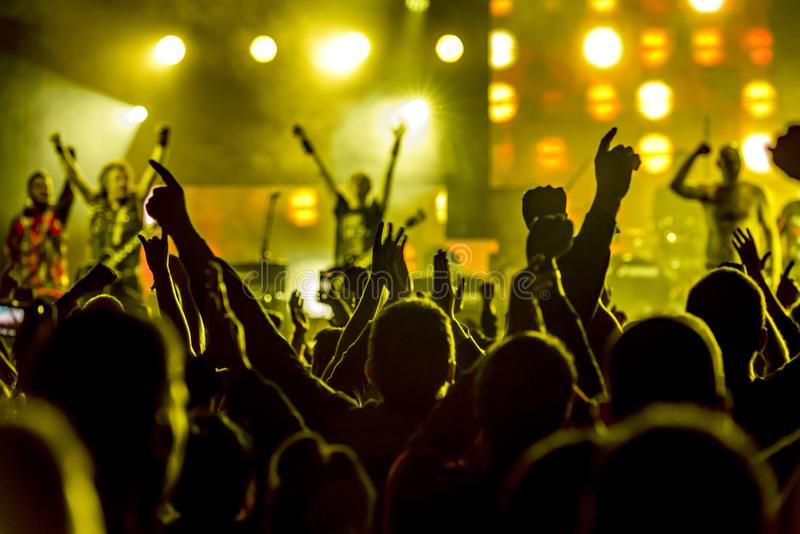 The crowd at the concert. Summer music festival. Silhouettes of concert crowd in front of bright stage lights. royalty free stock photos