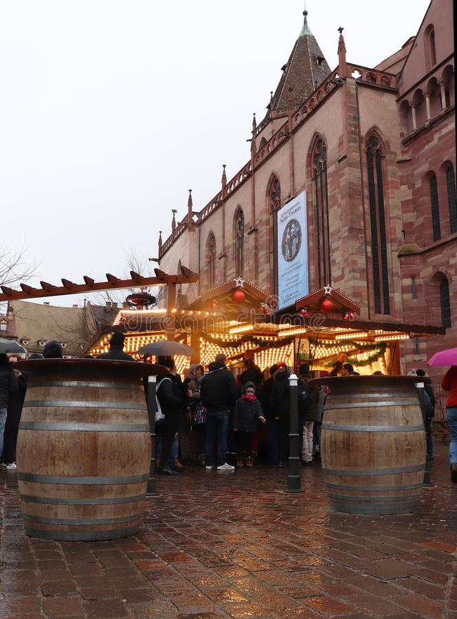 Crowd enjoying the Strasbourg, France Christmas Market. People gathered around a stall selling food and drink on a rainy day in Strasbourg, France during the royalty free stock image
