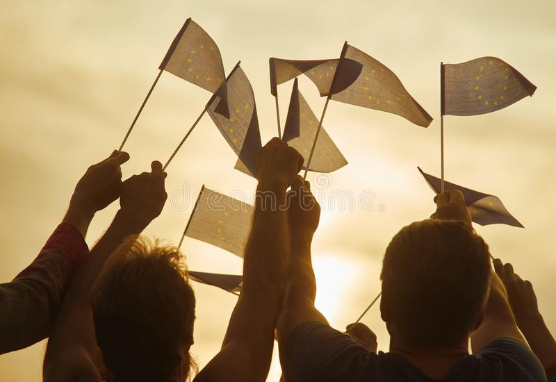 Crowd with EU flags. European people against morning sunshine background stock image