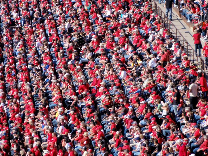 Crowd of Football fans wearing red clothes watching game royalty free stock photography