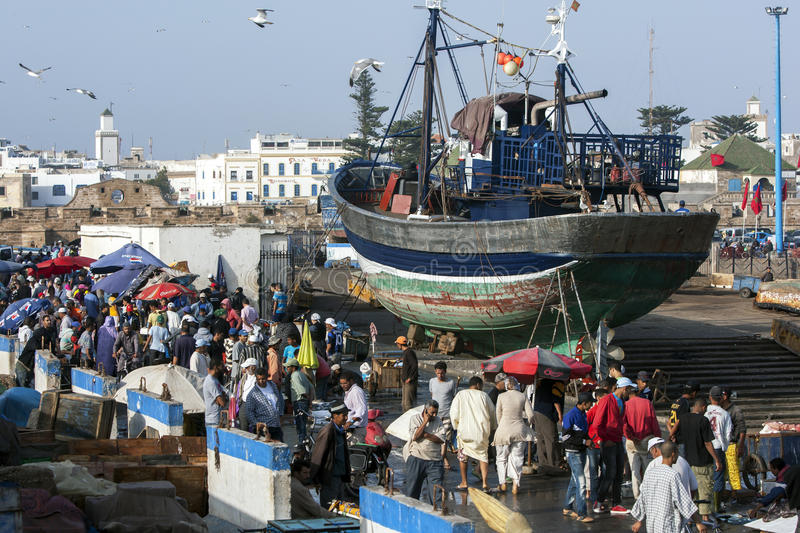 A crowd gathers along the dock of the fishing port in Essaouira in Morocco in the late afternoon. royalty free stock photography