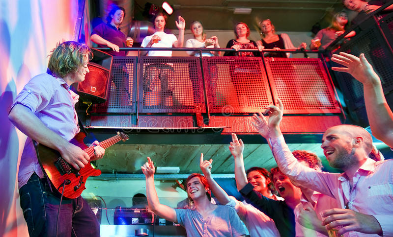 Crowd going wild. During a live performance of a guitarist in a club stock photos