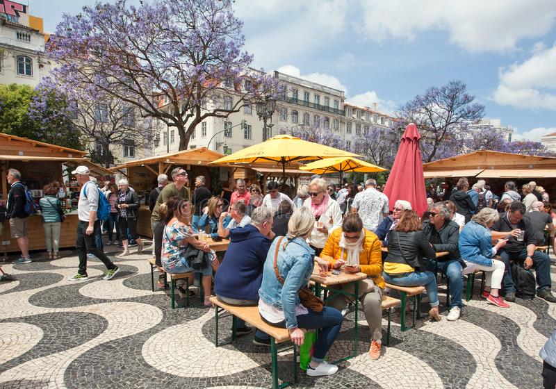 Crowd of hungry people meeting, eating and talking on square with fast food stores. LISBON, PORTUGAL: Crowd of hungry people meeting, eating and talking on royalty free stock images