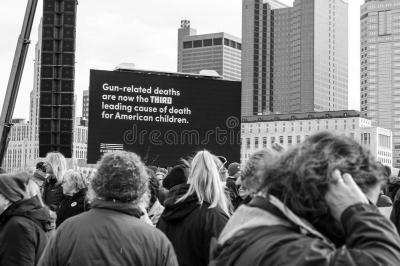 Crowd at March For Our Lives. Crowd standing before a sign at the March For Our Lives rally that states gun related deaths are the third leading cause of death royalty free stock image