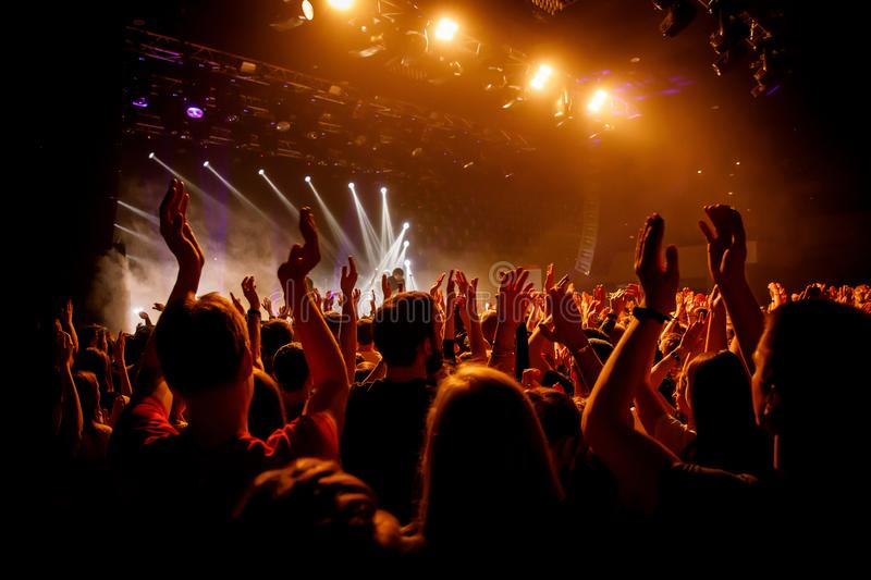 Crowd on music show, happy people with raised hands. Orange stage light royalty free stock images