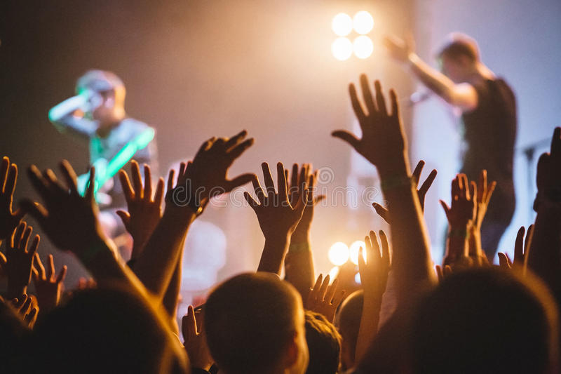 A crowd of people celebrating and partying with their hands in the air to an awesome rock artists. High ISO grainy image stock image