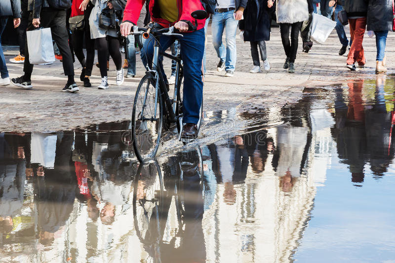Crowd of people and cyclist reflecting in a puddle royalty free stock image