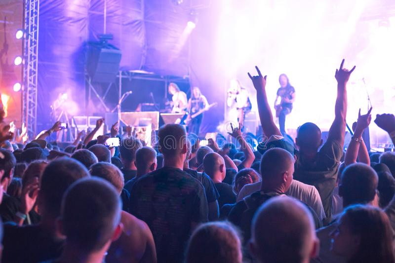A crowd of people with their hands up. A crowd of people dancing with their hands up dancing outdoors at a rock music festival royalty free stock photos