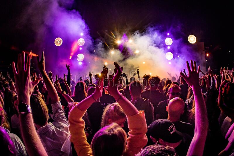 Crowd of people with hand in the air at an outdoor event royalty free stock photo