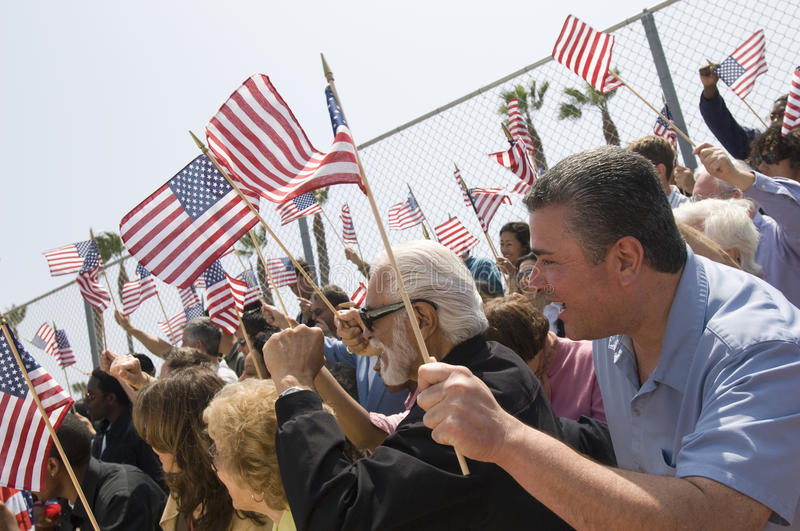 Crowd Of People Holding American Flag. Diverse group of people with American flag during a rally royalty free stock photography