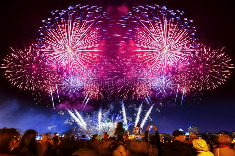 Crowd of people look at the new year fireworks , the concept of festivals and city celebrations. cheering crowd and royalty free stock photos