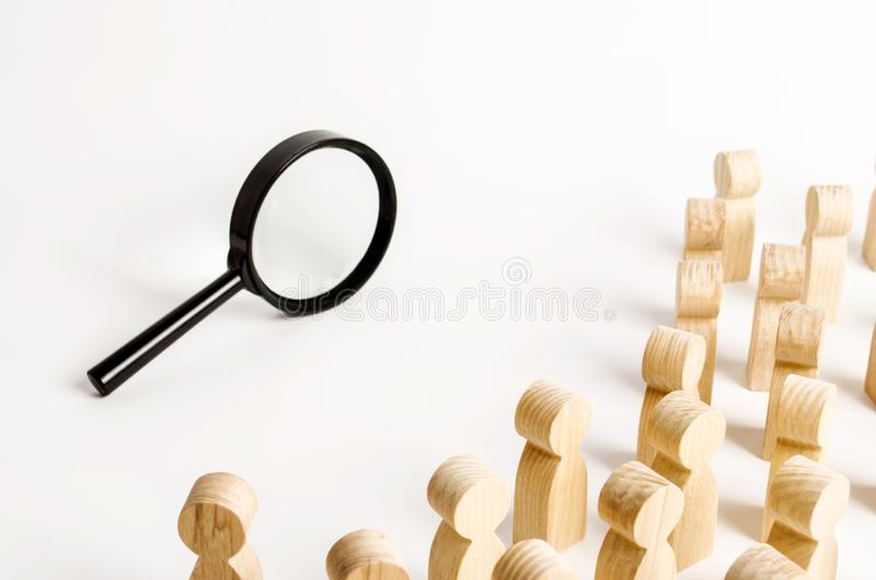 A crowd of people looking into a magnifying glass. Search and tracing concept, find out the truth. Find a solution to the problem royalty free stock photography