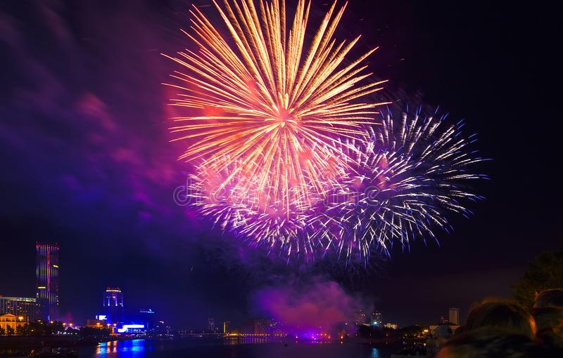 Crowd of people looking at Red, white and gold fireworks ver the sea with blue twilight sky background and city view stock photos