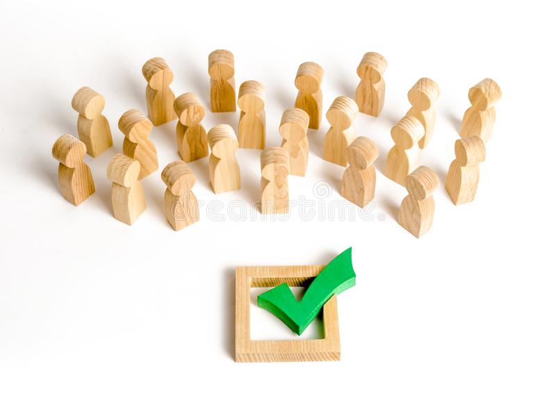 A crowd of people looks at a green check mark. Voting and election concept. Referendum, revolution. Forcible overthrow. Making the right decision, majority stock image