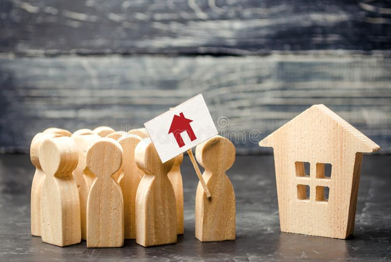 A crowd of people with a poster standing near the house. The concept of finding housing, a new home. High demand for housing royalty free stock images