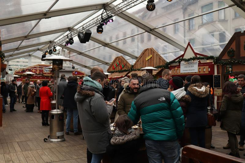 Crowd of people socializing in the beer tent in Ghent, Belgium. People in the alcohol tent at the Christmas Market in Ghent, Belgium on Christmas Eve royalty free stock photography