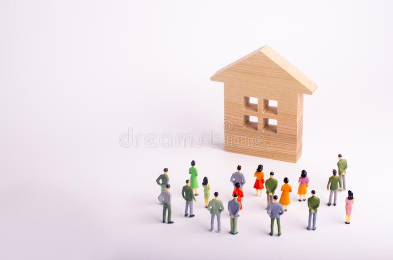 A crowd of people standing and looking at a wooden house on a white background. Buying and selling of real estate, rent. Affordabl. E housing. A group of stock photography