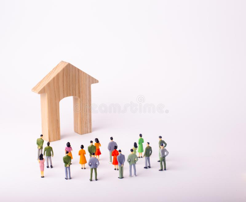A crowd of people standing and looking at a wooden house on a white background. Buying and selling of real estate, rent. Affordable housing. A group of royalty free stock image