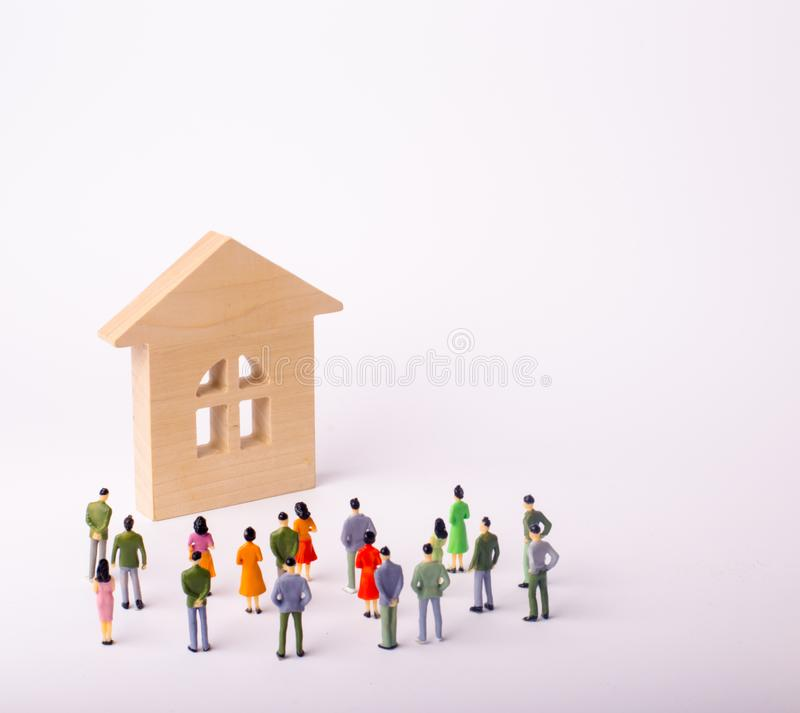 A crowd of people standing and looking at a wooden house on a white background. Buying and selling of real estate, rent. Affordable housing. A group of stock photo