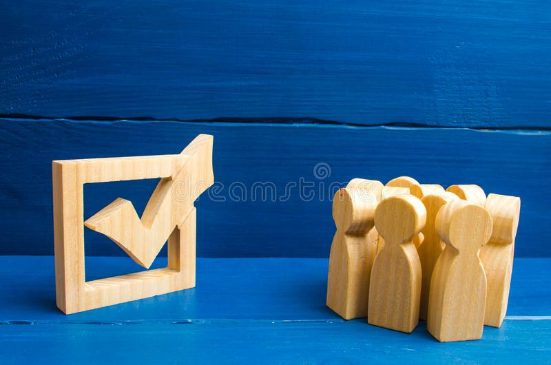 Crowd of people are standing near a huge tick in the box. Voters take part in voting for a president or a party. State elections, royalty free stock photos