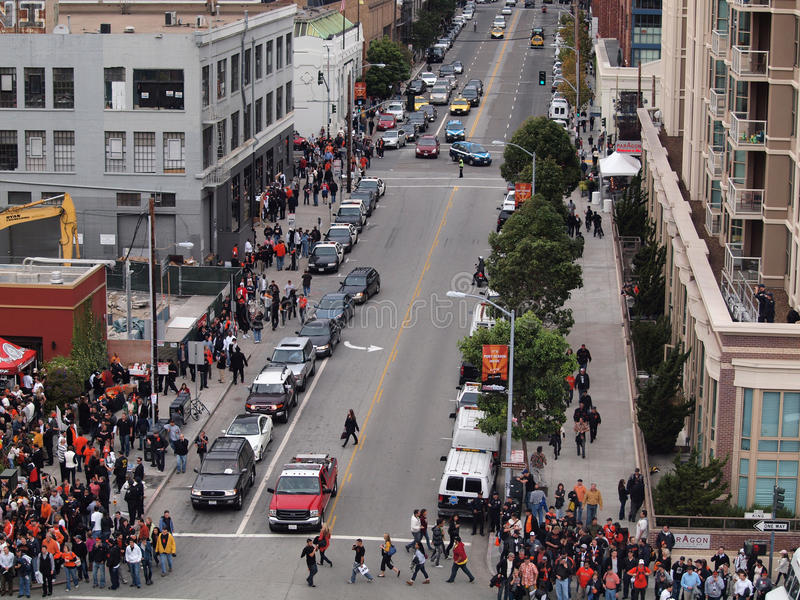 Crowd of people walk along sidewalk towards World Series game stock image