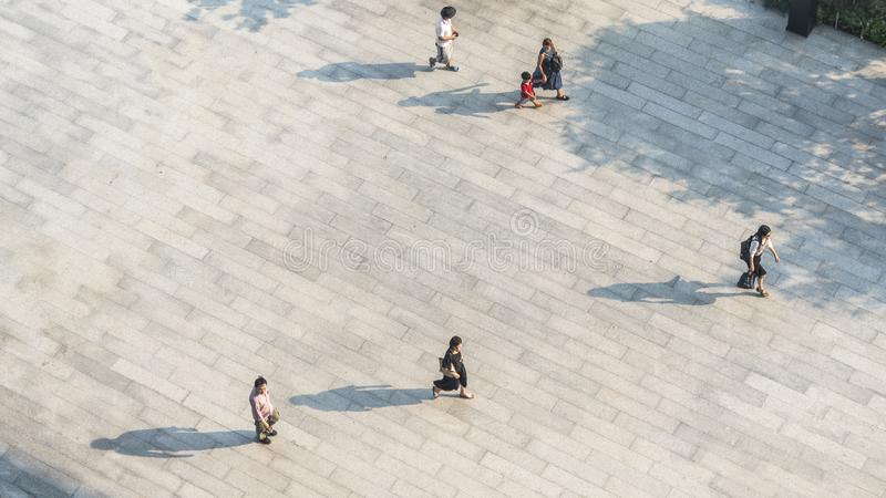 Crowd of people walk on open space concrete pavement from top vi royalty free stock image