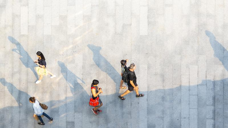Crowd of people walk on open space concrete pavement from top vi stock photos