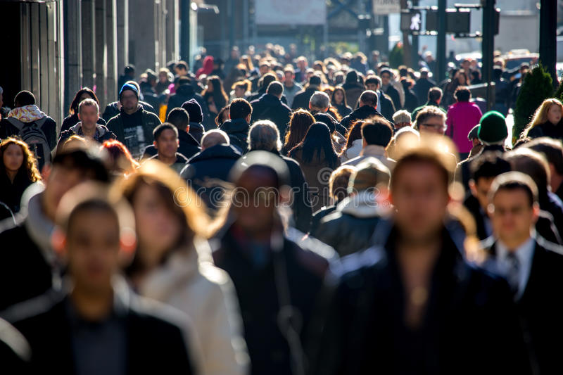 Crowd of people walking on city street stock photography