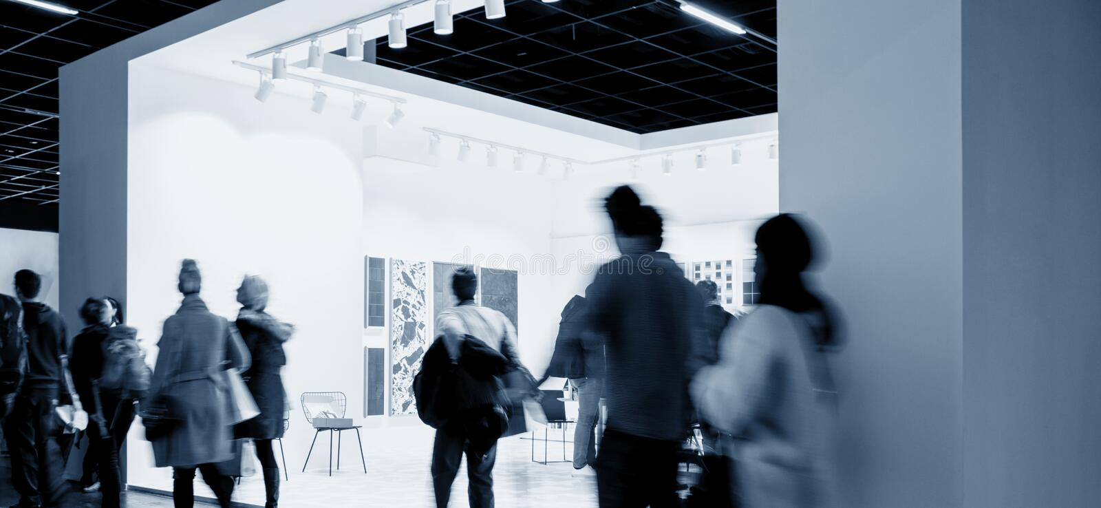 Business people crowd at an trade show booth. Crowd of people walking in a modern trade show booth. ideal for websites and magazines layouts stock image