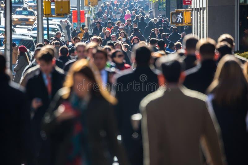 Crowd of people walking on street sidewalk stock image