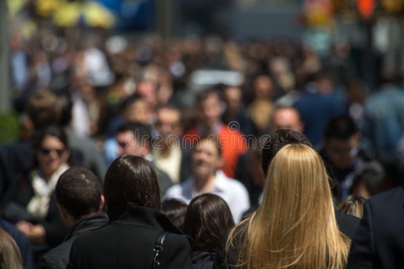 Crowd of people walking on street sidewalk royalty free stock photography