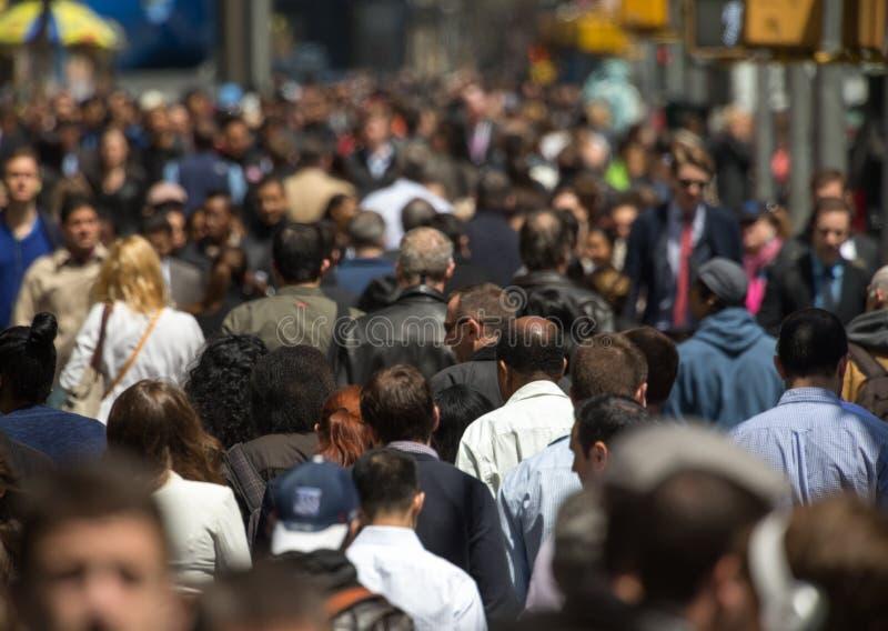 Crowd of people walking on street sidewalk stock photography