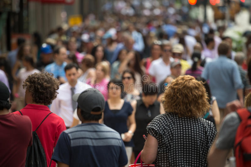 Crowd of people walking on street sidewalk stock photo