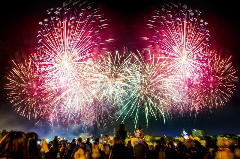 Crowd of people watch the city fireworks , new year celebration , night, metropolis royalty free stock images