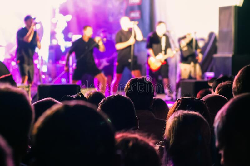 A crowd of people watching a musical group performing on stage stock photography