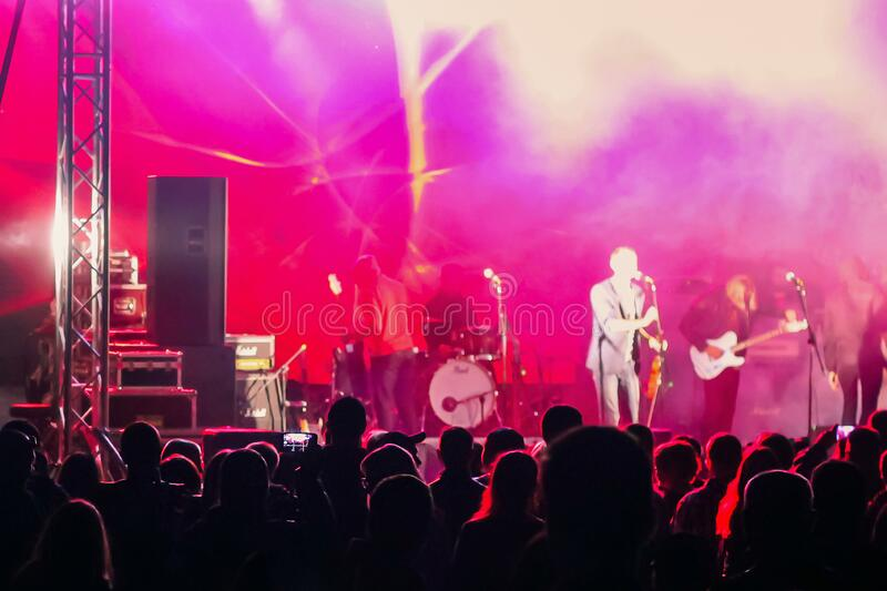 A crowd of people watching a musical group performing on stage royalty free stock images