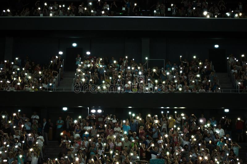 Crowd of people waving hands with mobile phone lights royalty free stock images