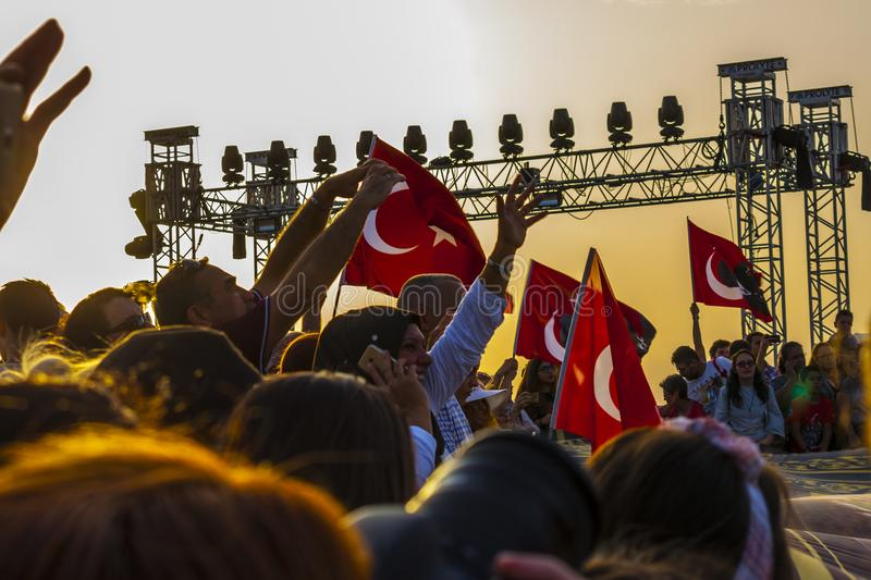 Turkish crowd in the sunset commemorating liberation from greeks. A crowd of people is waving many turkish flags in the sunset in Izmir to commemorate the stock images