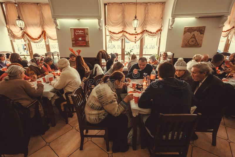 Crowd of poor people having lunch at the Christmas charity dinner for the homeless. KYIV, UKRAINE - JAN 7: Crowd of poor people having lunch at the Christmas royalty free stock photo