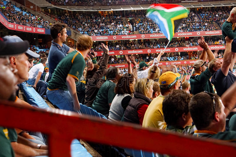 Crowd at Rugby Match. Crowd watching a Rugby match between Australia and South Africa at Pretoria. Spectator waving a South African flag