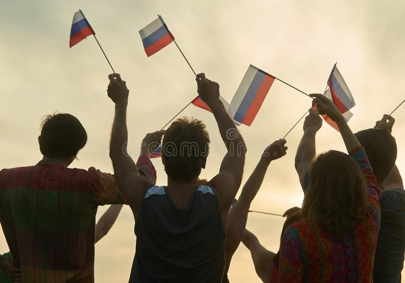 Crowd with russian flags. Evening sunny sky background stock photography