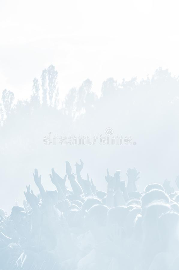Crowd of spectators at a concert in light blue tonality. High key background with a people on an open playground at a concert. Abstract soft focus image with royalty free stock images