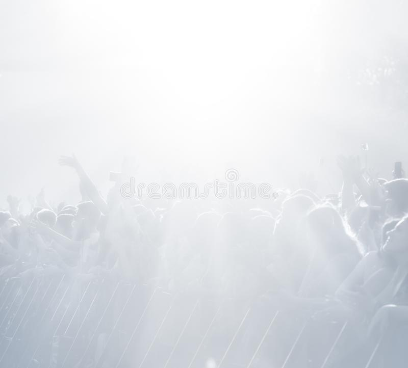 Crowd of spectators at a concert in light blue tonality. High key background with a people on an open playground at a concert. Abstract soft focus image with stock images