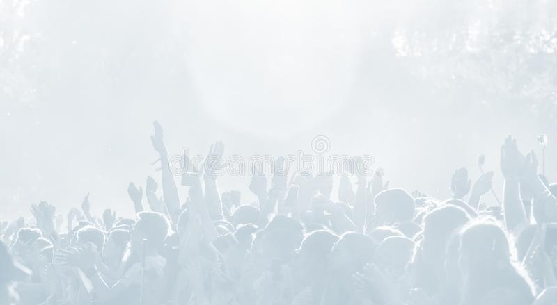 Crowd of spectators at a concert in light blue tonality. High key background with a people on an open playground at a concert. Abstract soft focus image with stock photography