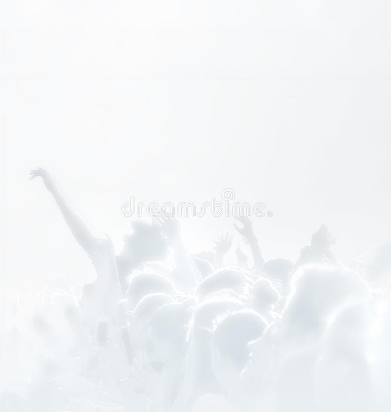 Crowd of spectators at a concert in light blue tonality. High key background with a people on an open playground at a concert. Abstract soft focus image with royalty free stock photos