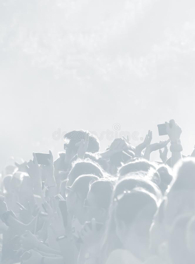 Crowd of spectators at a concert in light blue tonality. High key background with a people on an open playground at a concert. Abstract soft focus image with stock photos