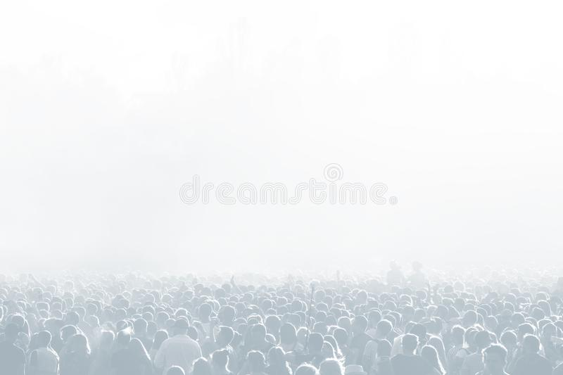 Crowd of spectators at a concert in light blue tonality. High key background with a people on an open playground at a concert. Abstract soft focus image with stock photo