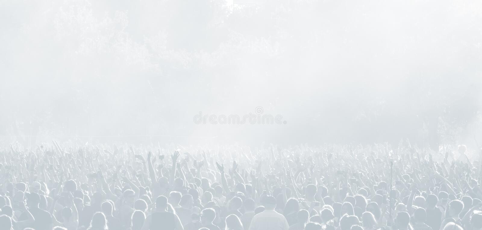Crowd of spectators at a concert in light blue tonality. High key background with a people on an open playground at a concert. Abstract soft focus image with royalty free stock photography