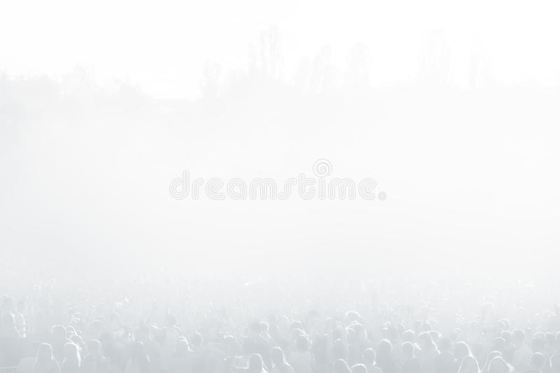 Crowd of spectators at a concert in light blue tonality. High key background with a people on an open playground at a concert. Abstract soft image with copy stock photography